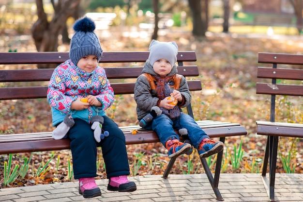 Crianças, sentando, banco, parque