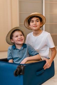 Crianças sorridente em foto média sentadas na bagagem