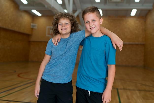 Crianças sorridente em tiro médio no ginásio da escola