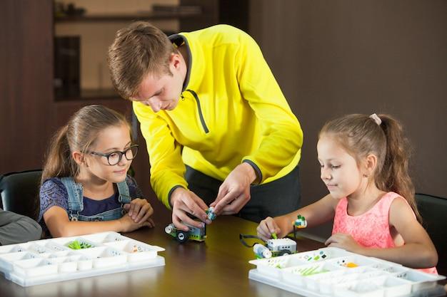 Crianças sorridentes alegres estão construindo um construtor.