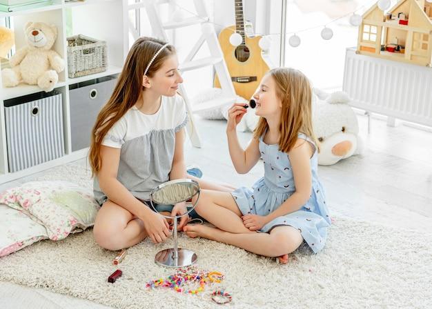 Crianças sorridentes aplicar maquiagem cosméticos