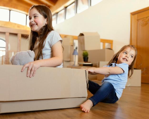 Crianças sorridentes brincando com a caixa