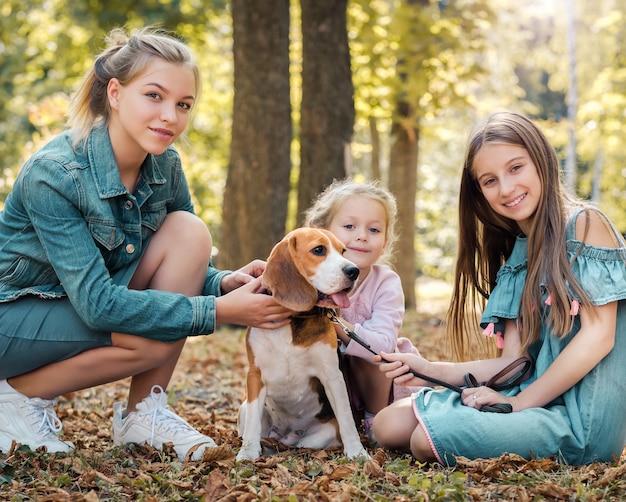 Crianças sorridentes brincando com um cachorro no parque durante o outono