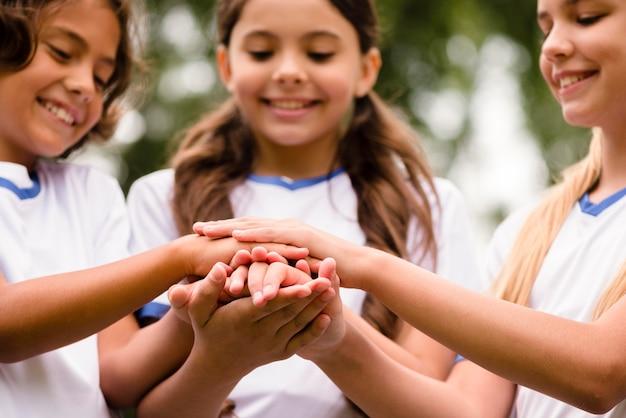 Crianças sorridentes colocando as mãos uns nos outros