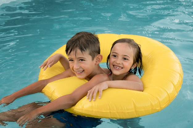 Crianças sorridentes de tiro médio com bóia salva-vidas