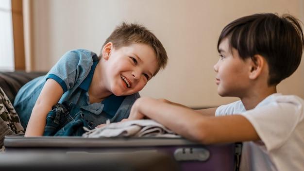 Crianças sorridentes de tiro médio fazendo malas