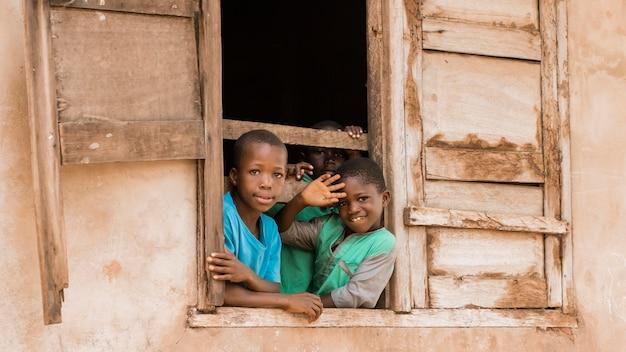 Crianças sorridentes de tiro médio na janela