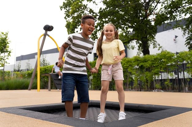 Crianças sorridentes em cena completa pulando juntas