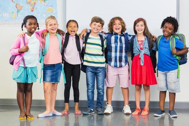 Crianças sorridentes em pé com o braço na sala de aula