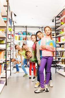 Crianças sorridentes em uma fila e brincando na biblioteca entre as estantes