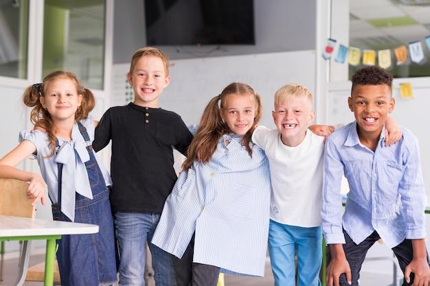 Crianças sorridentes posando juntas na aula