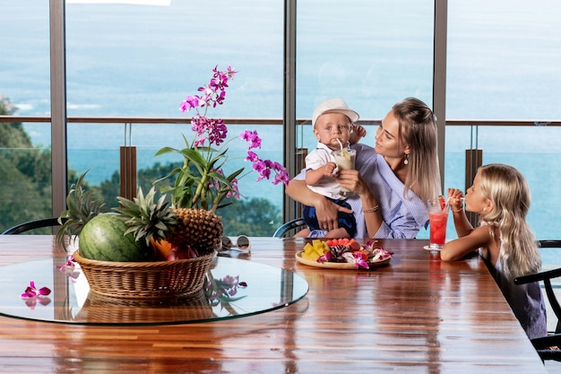 Crianças sorridentes tomando suco fresco de frutas tropicais na cozinha com a mãe