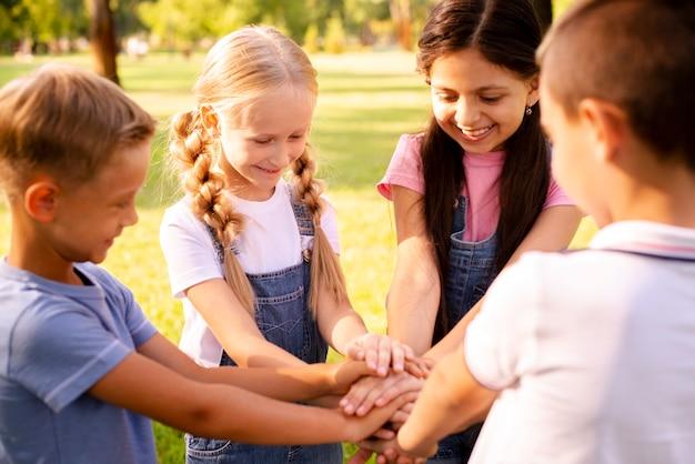 Crianças sorrindo, juntando as mãos