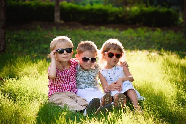 Crianças sorrindo no jardim em óculos de sol