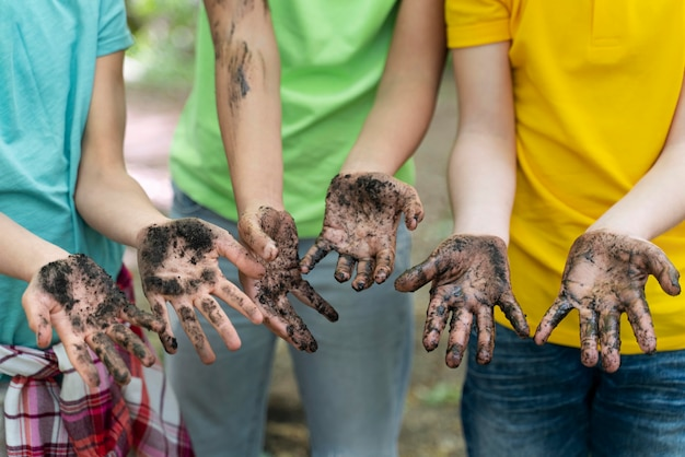 Crianças sujando as mãos após o plantio