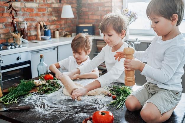 Crianças sujas e jovens vestidas com roupas casuais, aprendendo a cozinhar e a brincar com farinha na cozinha moderna em dias de sol.