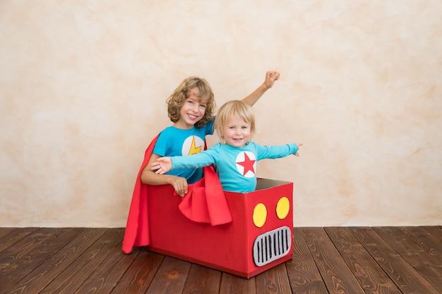 Crianças super-heróis brincando em casa