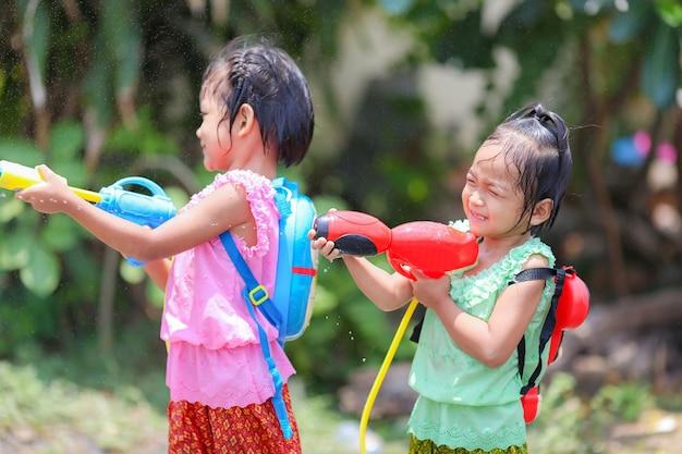 Crianças tailandesas brincando com armas de água no festival songkran com um vestido tailandês de época