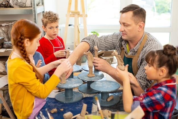 Crianças talentosas ouvindo o professor e esculpindo modelos de argila