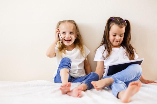 Crianças, tecnologia e conceito de casa meninas felizes com computadores de tablet pc
