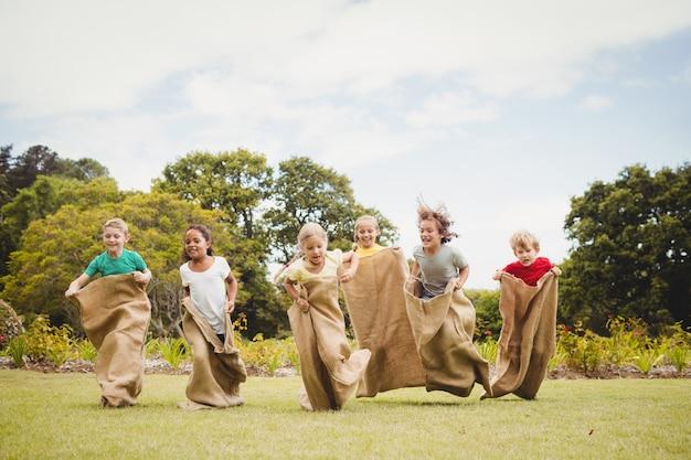 Crianças tendo uma corrida de sacos no parque