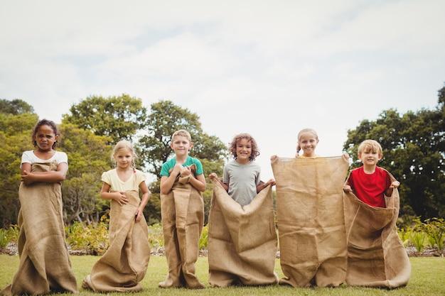 Crianças tendo uma corrida de sacos