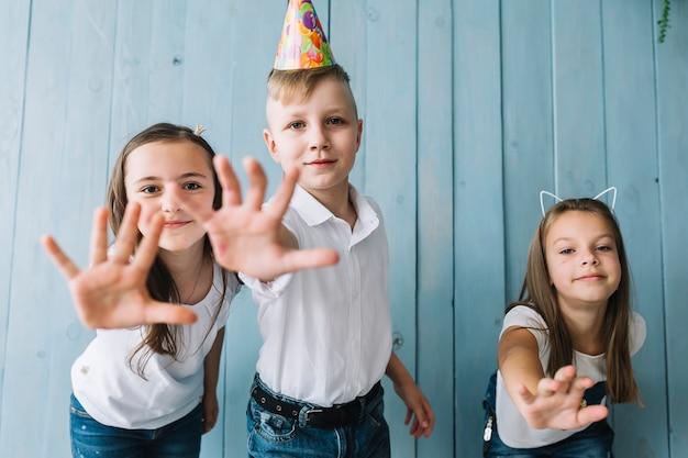 Crianças tentando alcançar a câmera na festa de aniversário