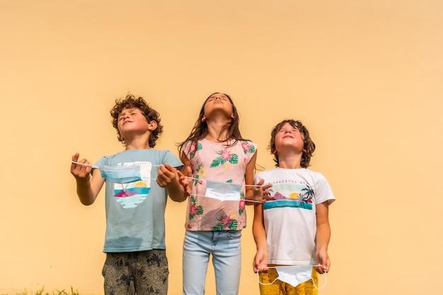 Crianças tirando as máscaras cirúrgicas em fundo laranja claro