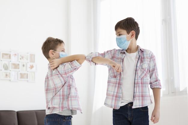Crianças tocando os cotovelos enquanto dentro e usando máscaras médicas