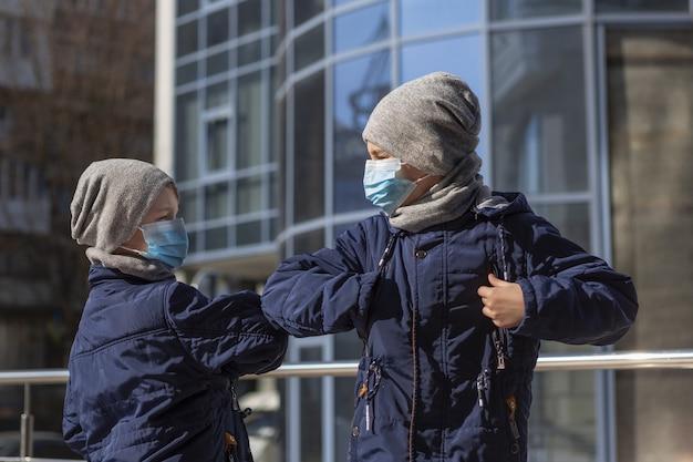 Crianças tocando os cotovelos enquanto usavam máscaras médicas fora