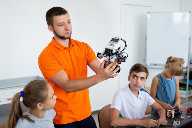 Crianças trabalhando com o professor em seu projeto de educação de robôs