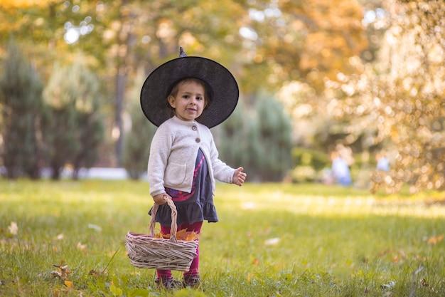 Crianças travessuras ou travessuras na noite de halloween, garotinha com balde de doces de cara de abóbora, truque infantil ou