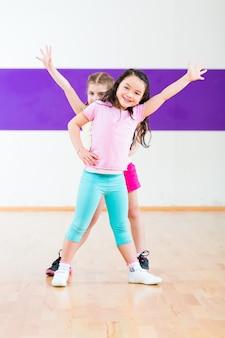 Crianças treinam fitness na escola de dança
