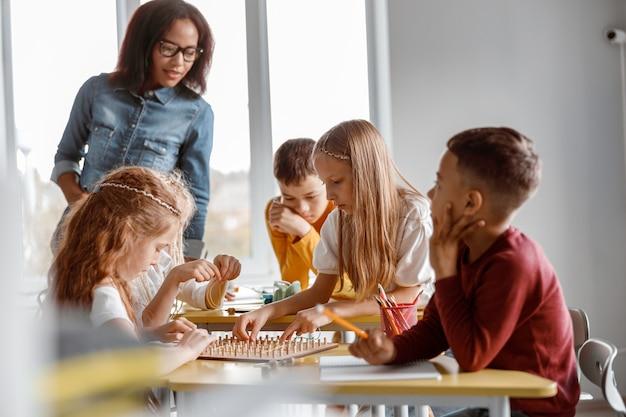 Crianças treinando habilidades analíticas e criativas em sala de aula