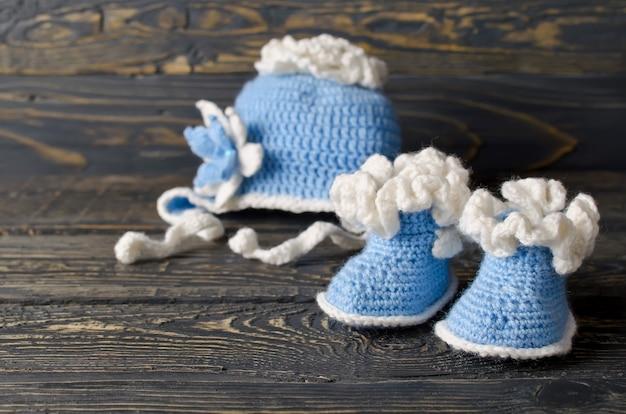 Crianças tricotam roupas para o menino. chapéu e sapatinhos