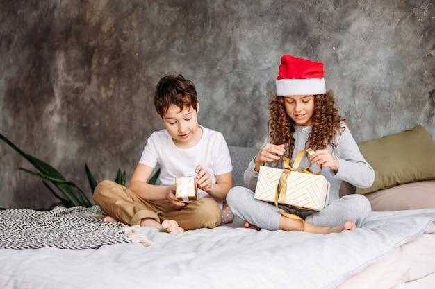 Crianças tween bonito em pijamas e chapéus de papai noel abrir caixas de presente de natal na cama com travesseiro, tempo de manhã de natal, festa de crianças