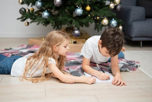 Crianças - um menino e uma menina escrevem cartas para o papai noel perto da árvore de natal na sala de estar