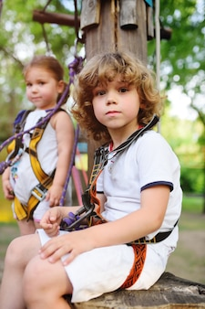 Crianças - um menino e uma menina no parque de corda passam os obstáculos.