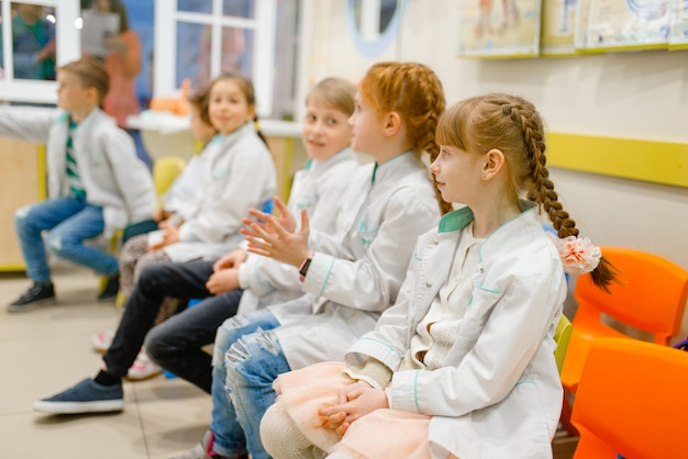 Crianças uniformizadas aprendendo a profissão de médico em sala de aula