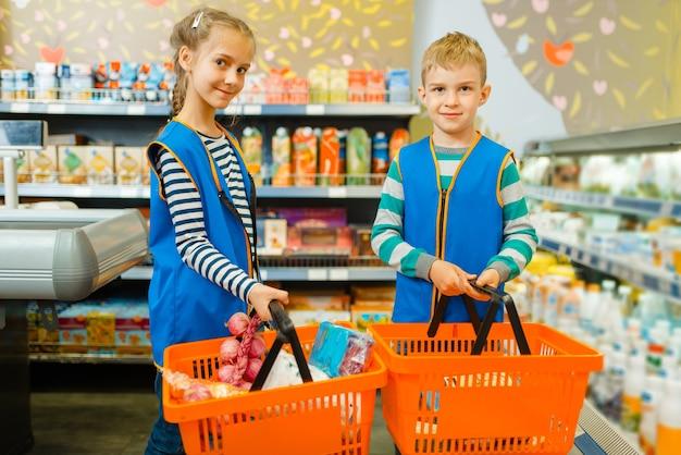 Crianças uniformizadas seguram cestas, menino e menina brincando de vendedores