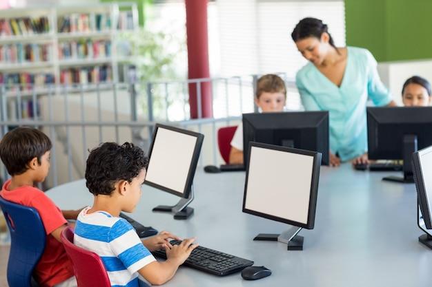 Crianças usando computadores como professor ensinando-os