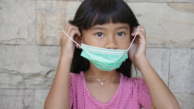 Crianças usando máscaras para se protegerem de vírus e poluição do ar