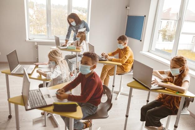 Crianças usando máscaras sentadas em suas carteiras na aula