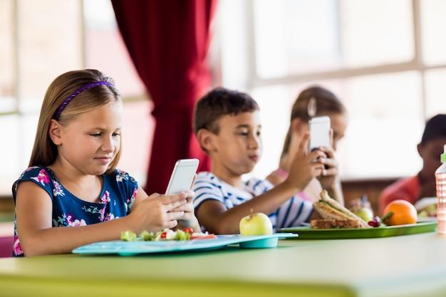 Crianças usando smartphones durante o almoço