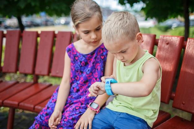 Crianças usando smartwatches com interesse e pais controlando novas tecnologias para crianças