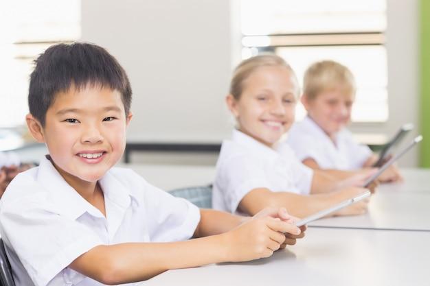 Crianças usando tablet digital em sala de aula