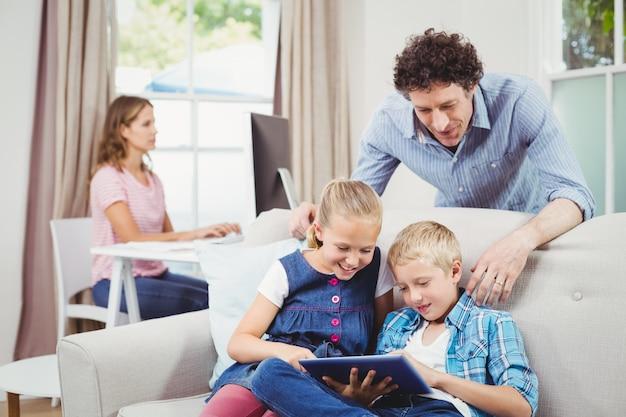 Crianças usando tablet digital enquanto pai olhando para eles