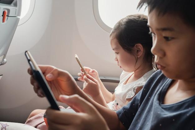 Crianças usando tablet em vôo, família viajando ao exterior com crianças