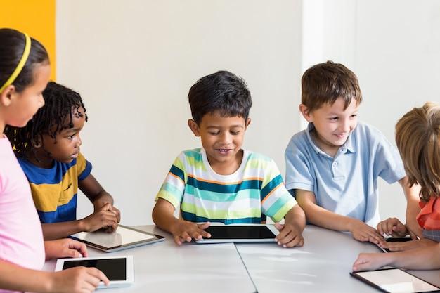 Crianças usando tablets digitais em sala de aula