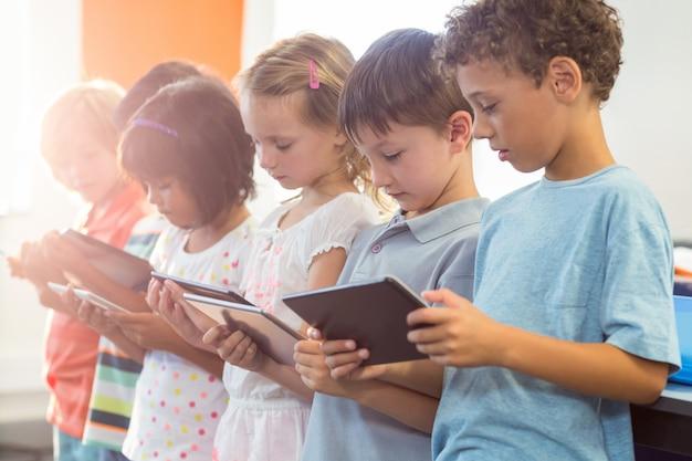Crianças usando tablets digitais